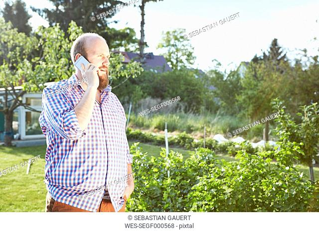 Young man with smartphone in garden, phoning