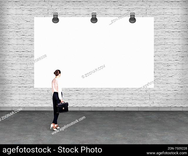 Elegant business woman standing and looking at blank white billboard. Copy-space for advertise