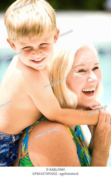Grandson hugging grandmother by swimming pool