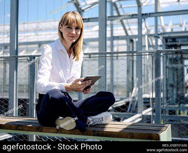 Smiling businesswoman using digital tablet while sitting on seat in greenhouse