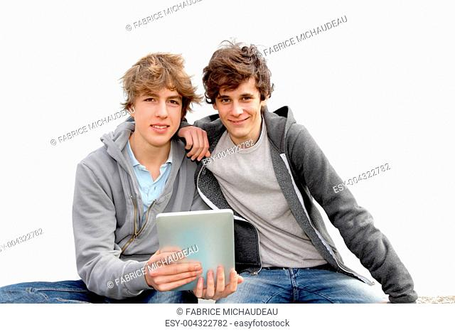 Teenage boys sitting outside with electronic tablet