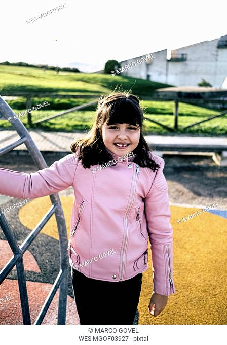 Portrait of smiling girl wearing pink leather jacket on playground