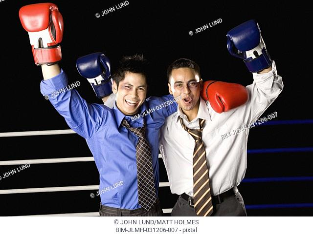 Two businessmen hugging and cheering in boxing ring