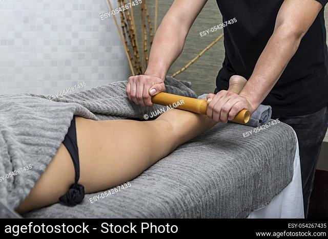 Crop man in modern center giving massage to woman with bamboo stick