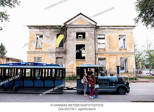 Kids talking to the driver of a tourist train in front of an empty house in Tallinn, Estonia, Europe