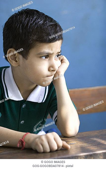 Young boy leaning on desk
