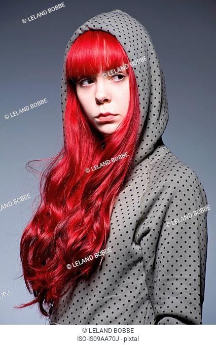 Young woman with long red hair in hooded top