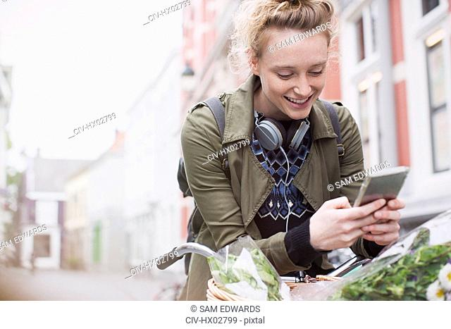 Smiling young woman texting with cell phone on bicycle on city street