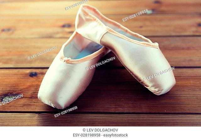 ballet, footwear and objects concept - close up of pointe shoes on wooden floor