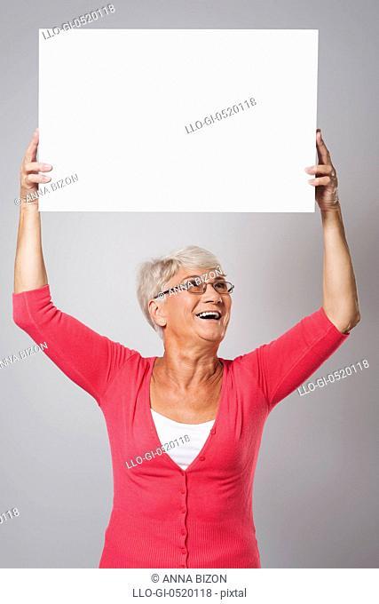 Beautiful senior woman holding whiteboard over the head. Debica, Poland