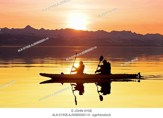 Kayakers paddle the calm waters of Alaska's Lynn Canal at sunset with the Chilkat Mountains in the background, Tongass National Forest, Alaska