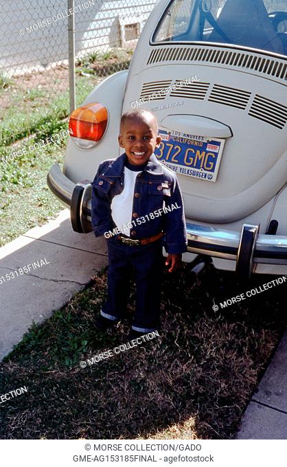 Portrait of a smiling African American boy, posing in front of a white 1972 VW Volkswagen Beetle parked in a driveway in Los Angeles, California, 1977
