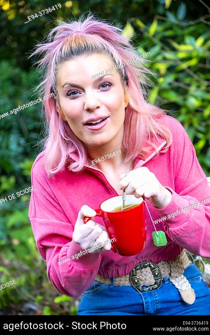 A beautiful 34 year old blond woman with a cup of tea smiling at the camera in a garden setting