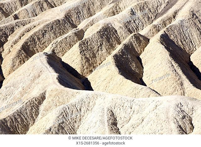 Sandstone formations near Zabriski Point in Death Valley have eroded into parallel lines of thin ridges with hiking trails on top