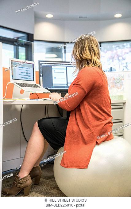 Caucasian businesswoman sitting on fitness ball in cubicle