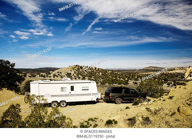 Car pulling trailer in desert landscape, Grand Staircase Escalante, Utah, United States