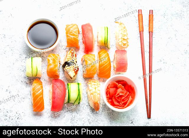 Assorted sushi set on white concrete background. Japanese sushi, rolls, soy sauce, ginger, chopsticks. Top view. Sushi nigiri. Japanese dinner/lunch