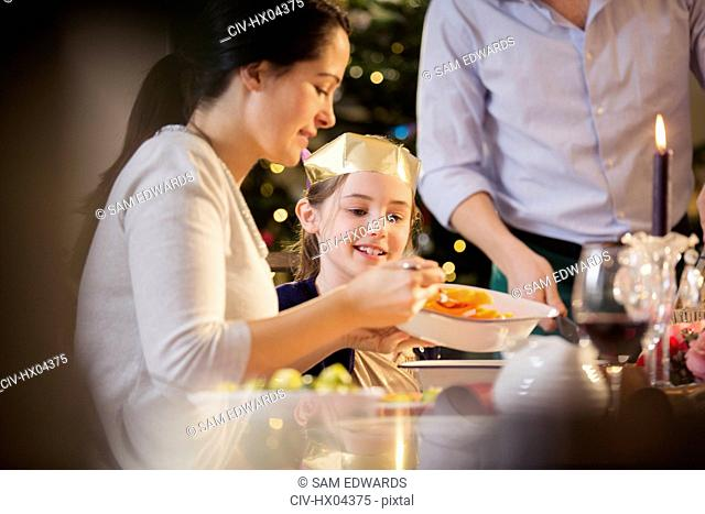 Mother serving carrots to daughter in paper crown at Christmas dinner
