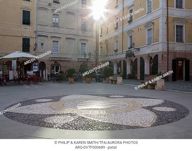 View across tiled piazza to buildings and sunshine