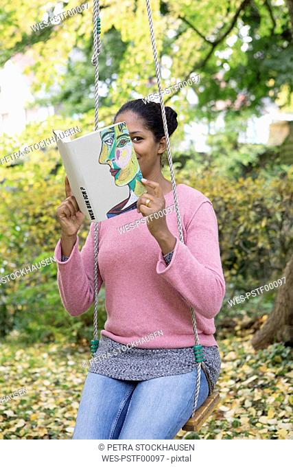Woman covering face with book, reading poetry in a garden