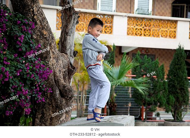 A small boy posing for photo in front of a residential building at Kam Tin, New Territories, Hong Kong