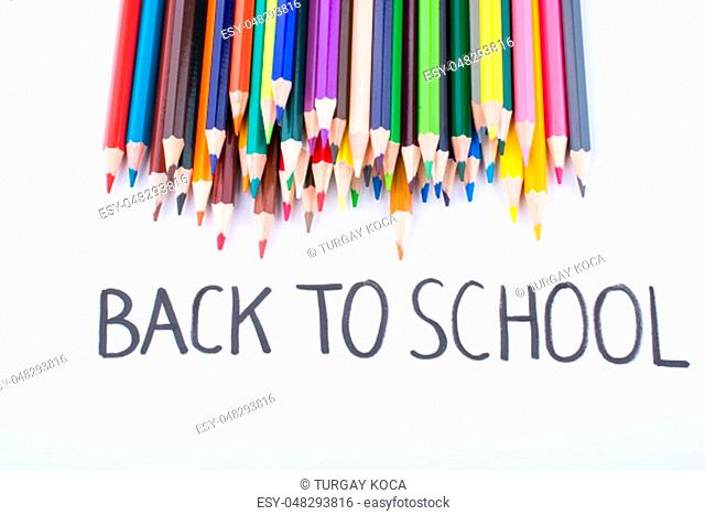 Color pencils and back to school title on a notebook