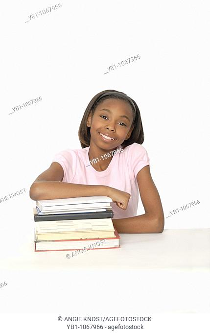 Smiling, confident female student with stack of books