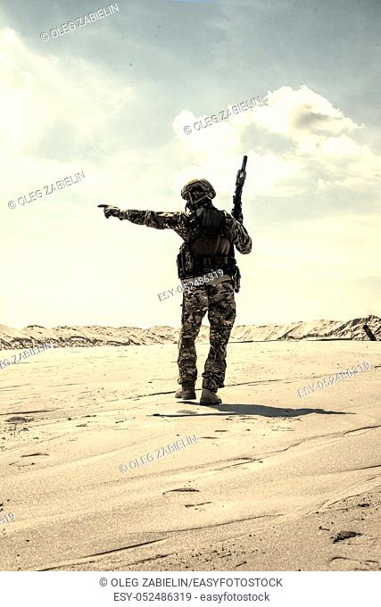 Soldier of special forces, infantry rifleman in military ammunition walking in desert and pointing on horizon. Military reconnaissance team leader managing dead...
