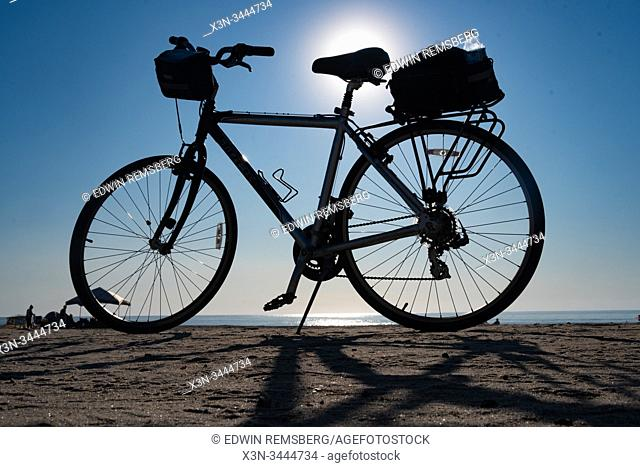 A bike parked at the beach on a clear day,