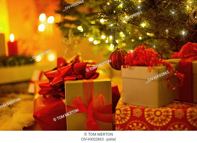 Christmas gifts with red bows under illuminated Christmas tree