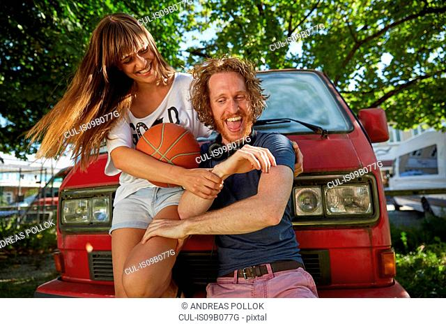 Young couple fooling around outdoors, laughing, young woman holding basketball