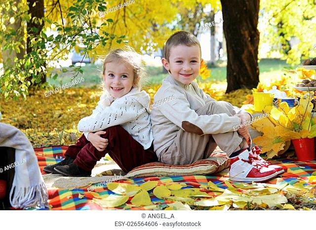 Smiling sister and brother sitting back to back under autumn tree