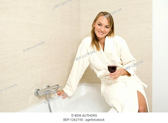 Young woman drinking wine while taking bath