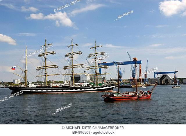Russian Tall Ship, Kruzenshtern, and other tall ships in front of the crane of the Howaldtswerke-Deutsche Werft, HDW Shipyard, in the Kiel Inner Fjord