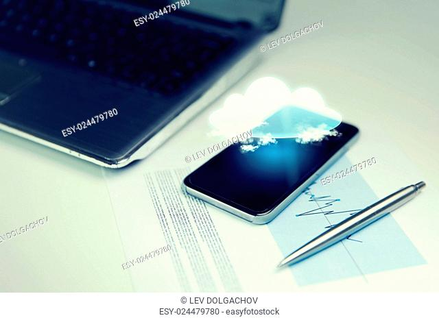 business, technology and information concept - close up of smartphone with cloud computing icon projection, laptop computer and chart with pen on office table