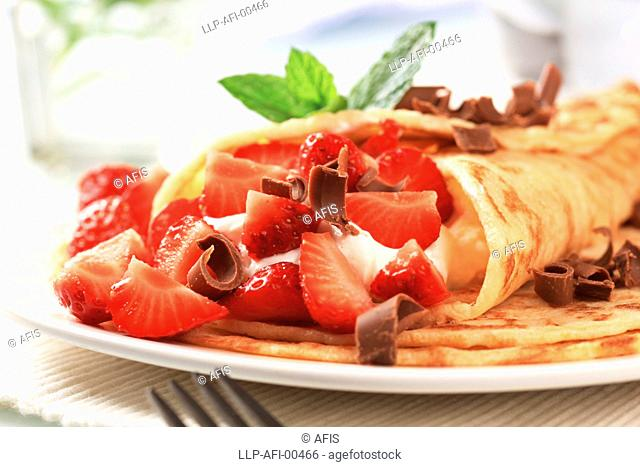 Crepes with cheese and strawberries sprinkled with chocolate curls