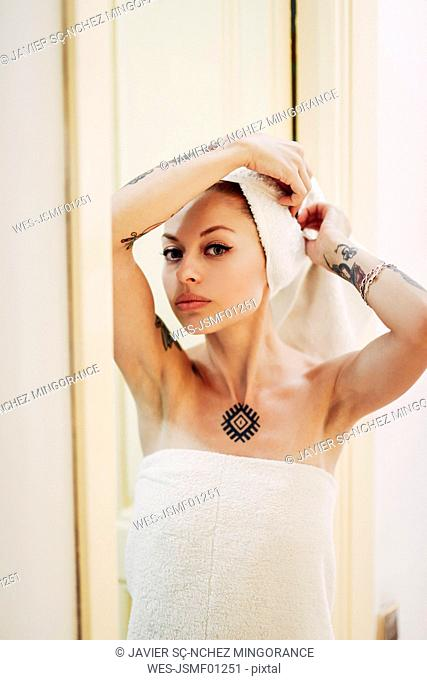 Portrait of tattooed woman at home with hair wrapped in a towel