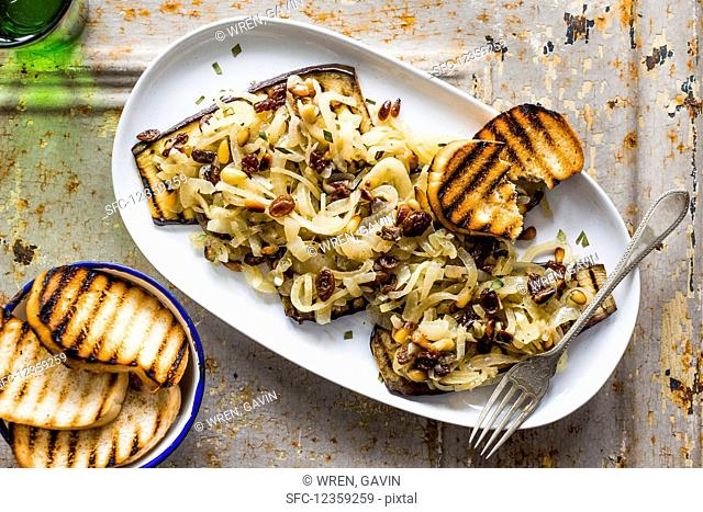 Traditional Venetian dish Melanzane in Saor made of grilled augergine with onions, raisins and pine nuts plus toasted bread slices on a white plate