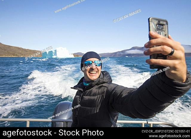 Traveller takes a selfie with iceberg from boat