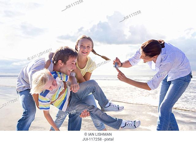 Family Taking Photos On Beach Vacation Together