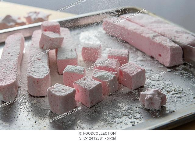 Marshmallows being dusted with icing sugar