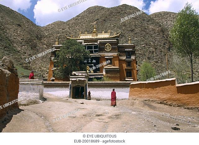 Labrang Monastery, elaborately designed building with a golden roof, partially obscured by a tree, and monks walking in the foreground