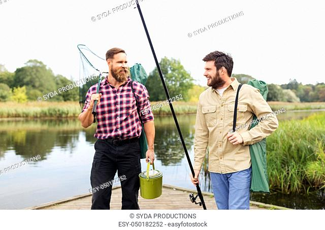 male friends with net and fishing rods on lake