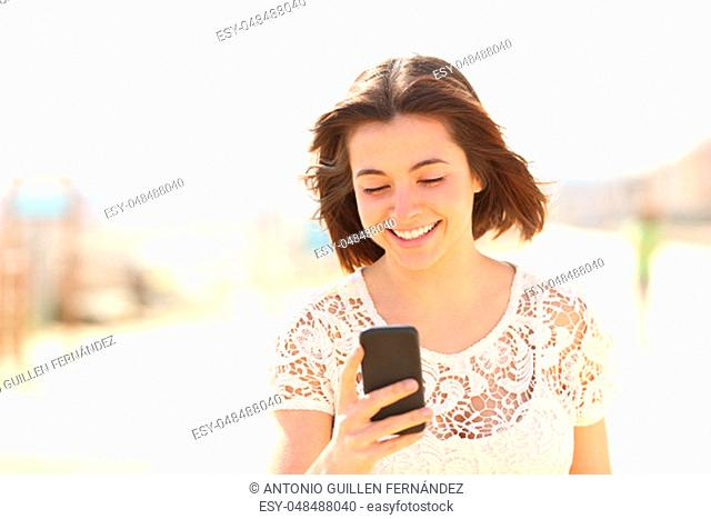 Front view of a happy woman walking towards camera checking phone content in a park