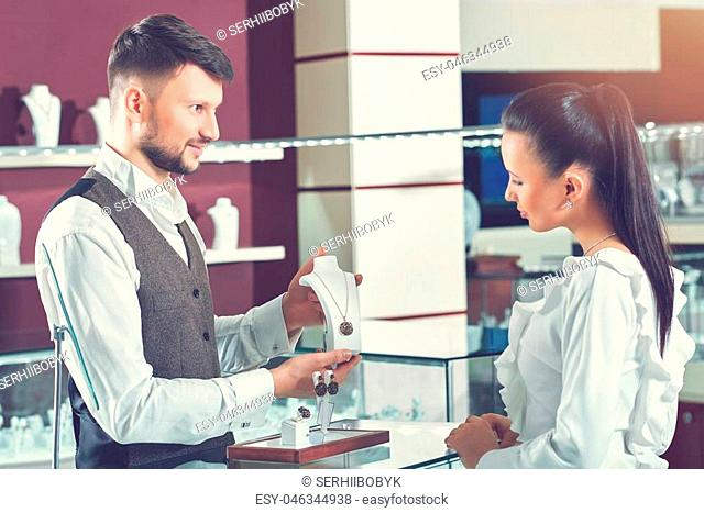 Helpful jeweler. Handsome young male jeweler selling a necklace at his store woman choosing jewelry at the shop client customer consumerism shopper buyer people...