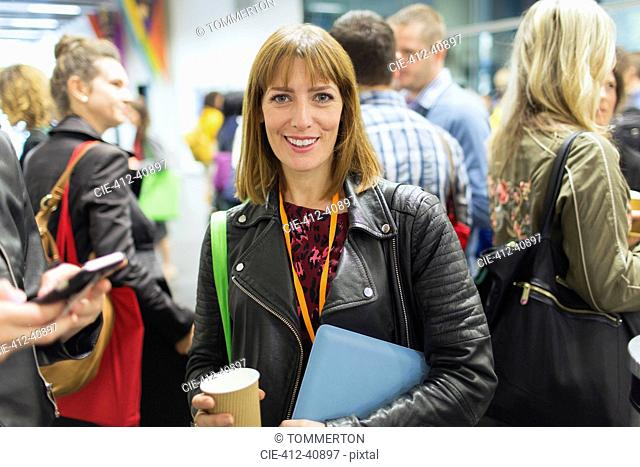 Portrait smiling, confident businesswoman drinking coffee at conference