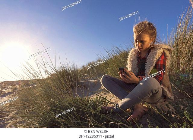 A young girl sits on the sand of a beach holding a digital device; Tarifa, Cadiz, Andalusia, Spain