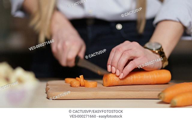 Woman's hand cutting carrot on board with knife