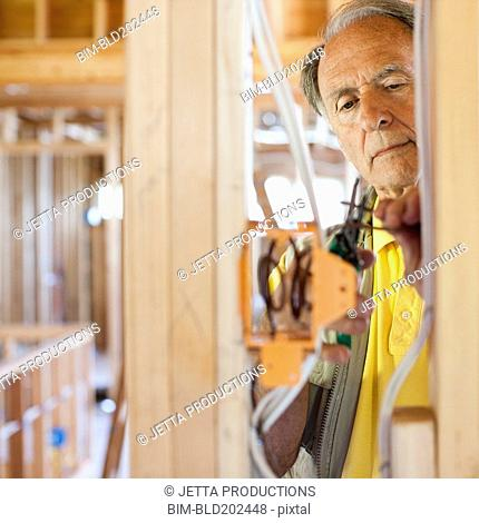 Caucasian electrician working on wiring in unfinished room
