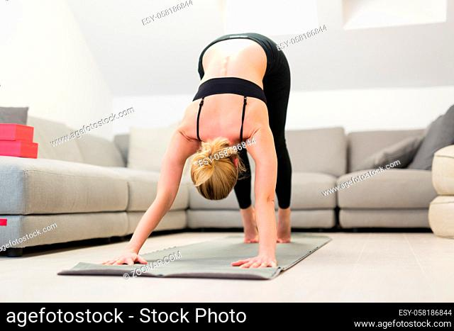 Beautiful blonde woman doing home workout indoors. Woman practice yoga at home. Fit girl using workout tutorials for healthy active lifestyle